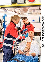 Paramedic putting oxygen mask on patient ambulance