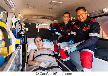 paramedic team and patient in ambulance - friendly paramedic...