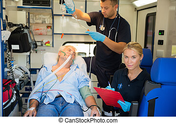 Paramedic treating injured patient in ambulance