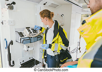 Paramedic using medical technology in ambulance car