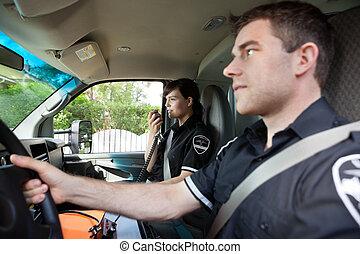 Paramedic with Radio in Ambulance - Paramedic talking on...