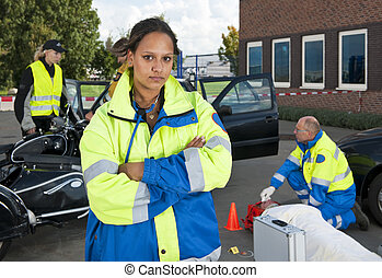 Young female paramedic posing confidently in front of a car accident site