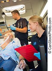 Paramedics examining injured patient in ambulance