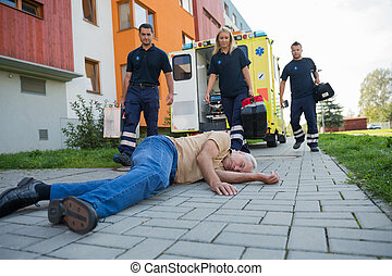 Paramedics giving help to injured senior man
