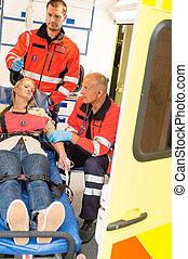 Paramedics help unconscious woman emergency aid