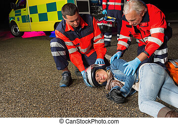 Paramedics helping motorbike driver lying on road -...