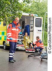 Paramedics helping woman bike accident ambulance