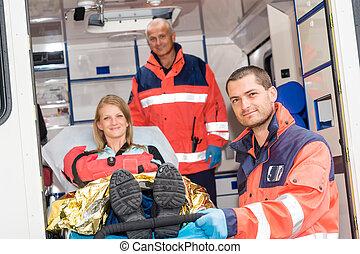 Paramedics helping woman on stretcher in ambulance