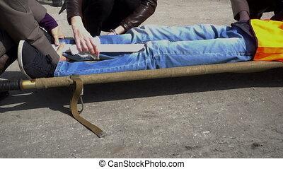 Paramedics immobilize victim's leg - Paramedics tending to...