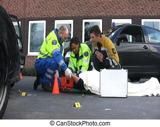 paramedics - Paramedics on the site of a car crash, taking...