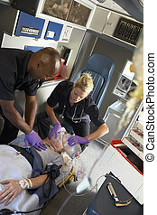 Paramedics performing CPR on patient in ambulance