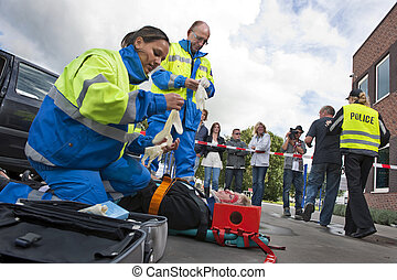 Paramedics tending to the first aid of an injured woman on a...