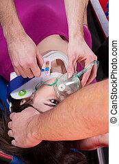 Paramedics using oxygen mask - Vertical view of paramedics...