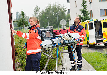 Paramedics with medical equipment ringing doorbell