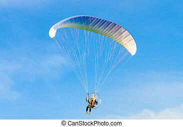 Paramotor on blue bright sky
