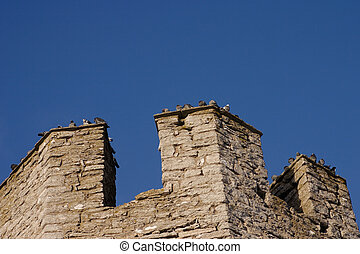 The top part of the tower in the Visby city wall witrh its parapet against a blue sky.