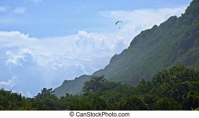Paraplan over green mountain
