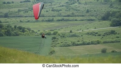 Person flying on paraplane above beautiful green rural meadow, active lifestyle, activity