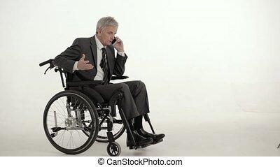 Paraplegic businessman on a wheelchair. Studio shot - Busy...