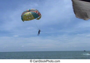 Parasail Takes Off From Beach - A parasailing tourist takes...