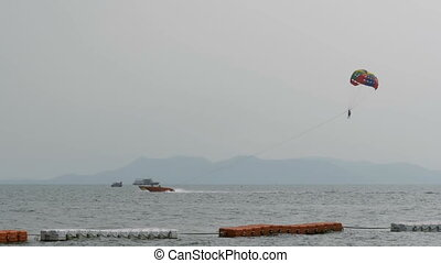 Parasailing, a man is flying on a parachute for a boat....