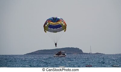 Parasailing behind a boat people flies over the sea on a...