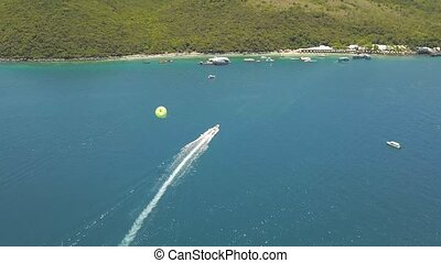 Parasailing in blue sea bay drone view. Aerial view sailing boat with paragliding in turquoise sea. Beautiful landscape blue lagoon and resort beach on island.