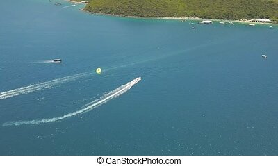 Parasailing in blue sea drone view. Aerial shot sailing boat in turquoise water in sea bay. Beautiful landscape blue lagoon and resort beach.