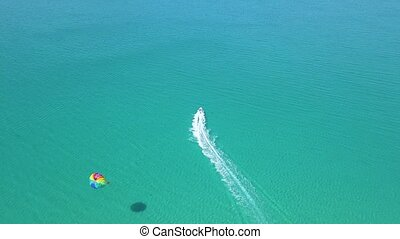 Parasailing in blue sea drone view. Parasailing summer activity and extreme entertainment while resting on resort beach. Colorful parasail wing pulled by sea boat in the sea water aerial view.