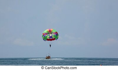 parasailing on sea, cutter have man with parachute in tow