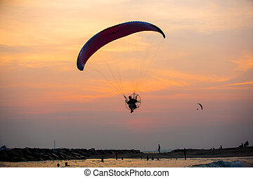 Parasailing under blue sky at sunset