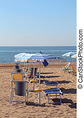 parasol and sunbeds on the sand of the tourist village by the se