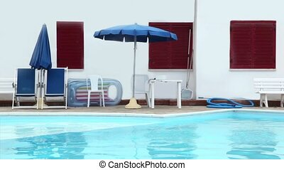 Parasols, chairs and other things are on edge of the pool