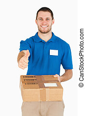 Parcel handed over by smiling young salesman giving thumb up
