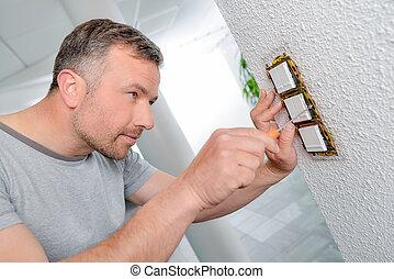 pared, el atornillar, tres, interruptores, hombre, fila