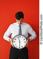 parede, homem, negócio, segurando, relógio