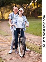 pareja adolescente, bicicleta que cabalga, juntos