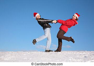 pareja, baile, en, nieve, colina, en, santa claus sombreros, 2