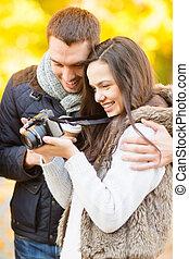 pareja, con, cámara fotográfica de la foto, en, otoño, parque