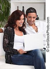 pareja, con, computador portatil, en, salón