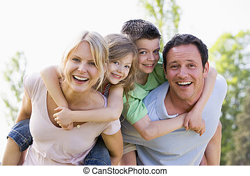 pareja, dar, dos, niños jóvenes, paseos de paseo sobre hombros, sonriente