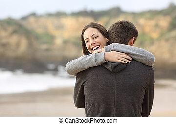 pareja, de, adolescentes, abrazar, en la playa