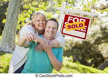 pareja, delante de, vendido, signo bienes raíces, tenencia, llaves