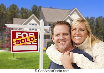 pareja, delante de, vendido, signo bienes raíces, y, casa