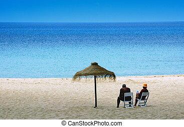 pareja, descansar, en la playa