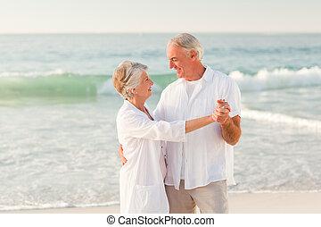 pareja edad avanzada, bailando, playa