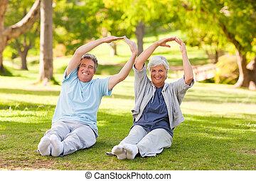 pareja edad avanzada, hacer, su, estira, en el parque