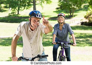 pareja, el gozar, paseo de la bici, en el estacionamiento