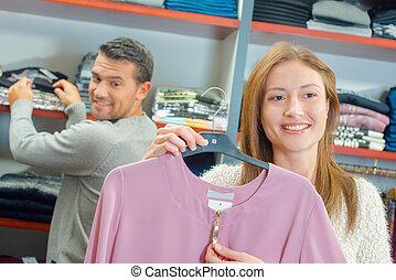 pareja, el hacer compras de las ropas, juntos