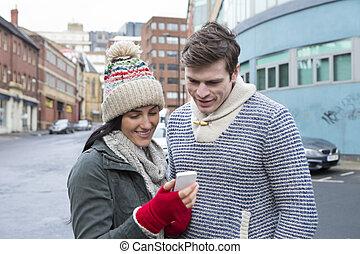 pareja, el mirar, un, smartphone, en la ciudad